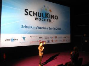 Film- und Umweltpädagoge Wolfgang J. Fischer lässt sich noch schnell vor der großen SchulKinoWochen-Leinwand von einer Schülerin fotografieren.