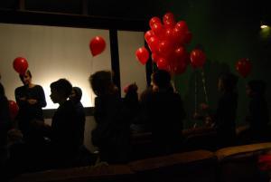"""Rote Ballons fliegen nach der Vorführug von """"Der rote Ballon"""" von der Kinoleinwand ins Regenbogenkino"""