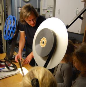 Die Kunst der Filmprojektion: Nach der Vorstellung besuchen die Grundschüler*innen die Projektionskabine im Kino Arsenal und lassen sich von Vorführer Anselm erklären, wie Filme für die Projektion vorbereitet werden.