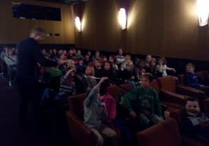 Filmvorführer zeigt den Schüler*innen einen Filmstreifen vor MORITZ IN DER LITFASSSÄULE